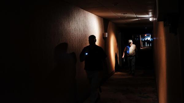Hotel guests walk through dark hallways in Fort Myers, Fla., on Sunday.