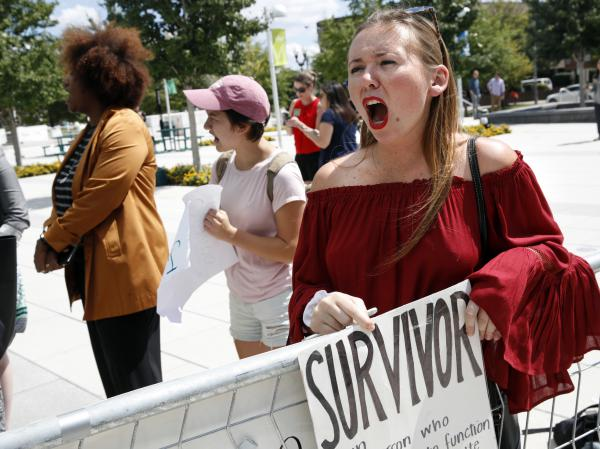 Meghan Downey, 22, a recent graduate from the College of William & Mary, protests outside an Arlington, Va., auditorium after Education Secretary Betsy DeVos spoke about campus sexual assault.