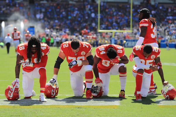 Terrance Smith #48, Eric Fisher #72, Demetrius Harris #84, and Cameron Erving #75 of the Kansas City Chiefs take a knee before the game against the Los Angeles Chargers at the StubHub Center on Sunday in Carson, Calif.