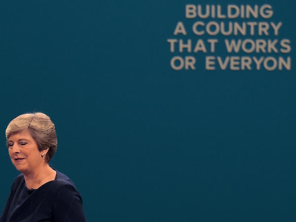 After delivering a speech in Manchester on Tuesday, Britain's Prime Minister Theresa May walks past a slogan whose letters fell off while she spoke.