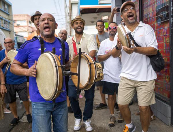 "Hector René ""Tito"" Matos (left), leads a celebratory plena musical bar hopping jam session along the trendy Calle Loiza neighborhood in San Juan, Puerto Rico."