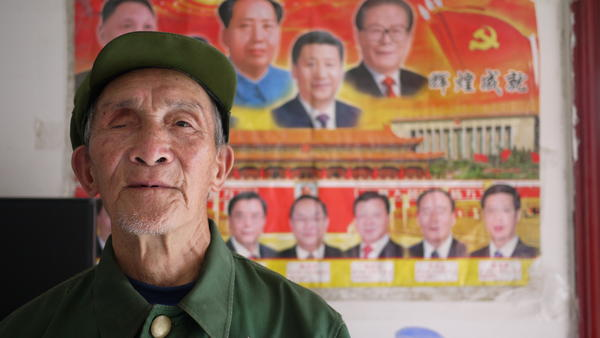 Yu Zu'en stands in front of one of the few wall decorations in his new, government-issued apartment: a poster of China's leaders. The 84-year-old veteran lost his right eye fighting the Americans in Korea in 1951.