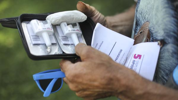 A man checks out an anti-overdose kit he was given at a clinic. With America confronting an opioid epidemic, Walgreens says it will stock naloxone spray at all of its pharmacies.