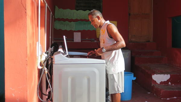 "Roberto ""Coco"" Viruet washes clothes in the community laundry room in La Perla. Viruet says it's been ""too long"" without power in his neighborhood."