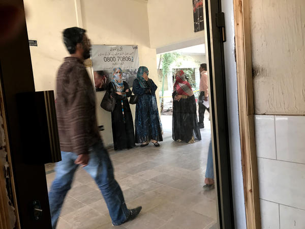 Friends of Nawaz Atta, a missing activist, accompany his mother at a police station to report the man's disappearance. Atta was taken by armed men in late October.
