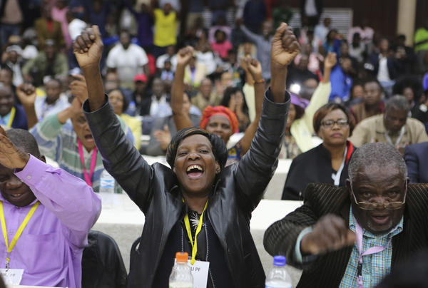 Members of the ZANU-PF Central committee react after the ruling party fired longtime President Robert Mugabe in Harare on Sunday.
