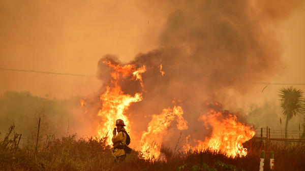 Fire and smoke rise off the northbound side of the U.S. 101 freeway in La Conchita, Ventura County.