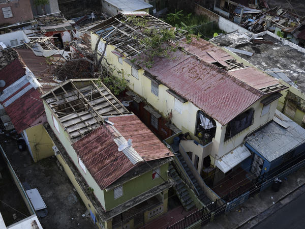 This photo taken last month in San Juan, Puerto Rico, shows roofs damaged by Hurricane Maria and the interior of buildings still exposed to the elements.