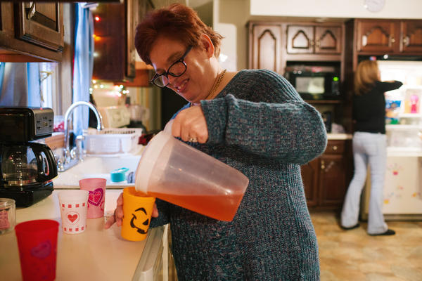 Pauline helps pour juice for dinner at her group home.
