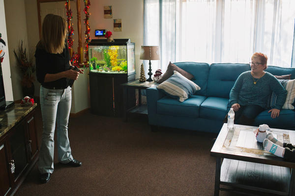 Roxanne Kiehart, one of the caretakers at Pauline's group home, puts in a movie for Pauline and a housemate after they returned home from a day program.