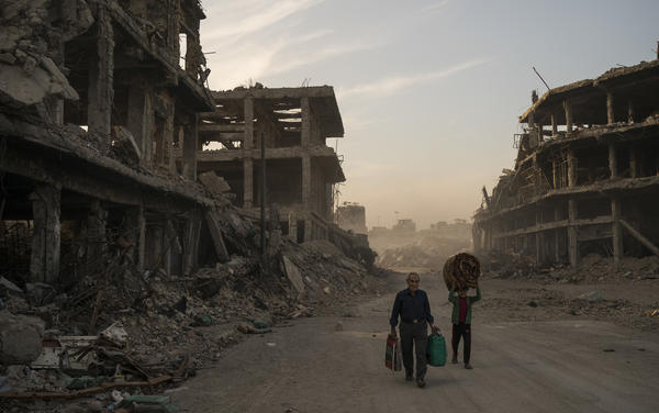 Two civilians carry belongings they collected from their damaged house in the Old City of Mosul, Iraq. The Islamic State controlled the northern Iraqi city for three years before being driven out last year. ISIS no longer controls any cities, but small groups of fighters remain in Iraq and Syria, and are still considered a threat.