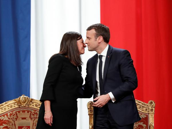 French President Emmanuel Macron kisses Paris Mayor Anne Hidalgo at Paris' city hall after his inauguration last May. Another French female mayor told her local council members in December she would no longer greet them with the traditional two-cheek kiss but, rather, with a handshake.