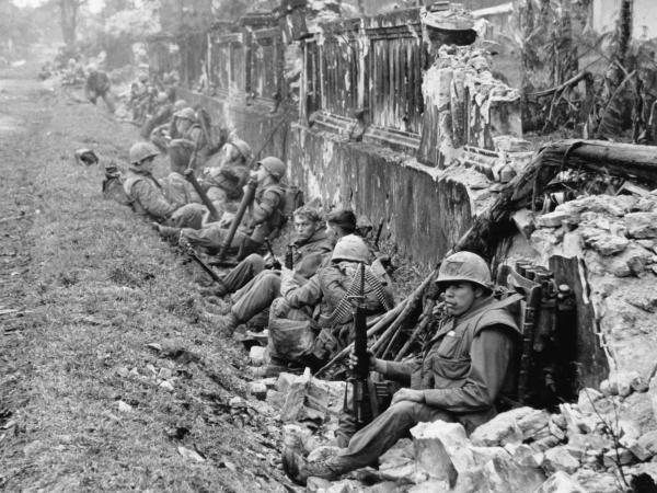 A unit of the 1st Battalion, 5th Marine Regiment, rests alongside a battered wall of Hue's imperial palace after a battle for the citadel in February 1968, during the Tet Offensive.