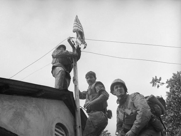 Members of Alpha Company of the 1st Battalion, 5th Marine Regiment, raise the U.S. flag on the south wall of the citadel in Hue after weeks of fierce fighting and heavy casualties.