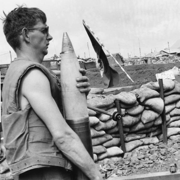 A U.S. Marine carries a 155 mm shell at Khe Sanh in January 1968. North Vietnamese troops attacked the remote outpost to serve as a diversion in the leadup to the Tet Offensive.