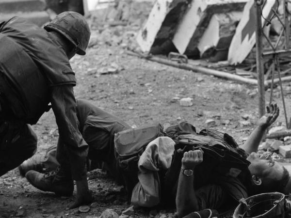 Keeping his head low against North Vietnamese snipers, a medical corpsman scurries to help a U.S. Marine in Hue street fighting during the Tet Offensive.