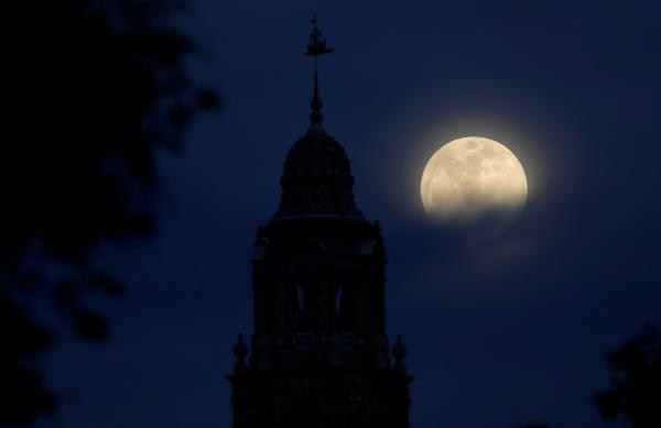 A blue moon rises over Balboa Park's California Tower in San Diego.