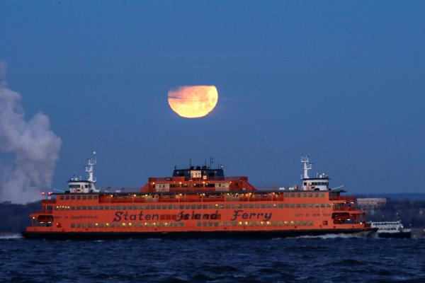 The super blue blood moon sets behind the Staten Island Ferry, as seen from Brooklyn, New York.