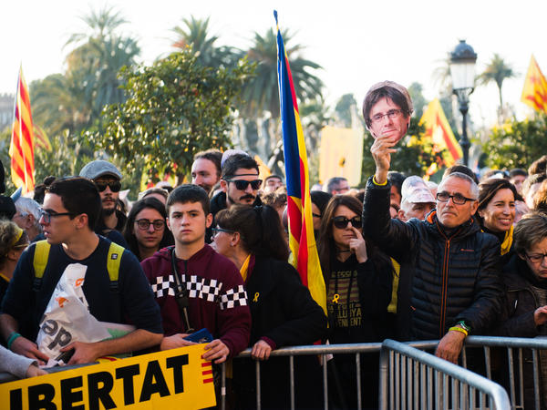 Demonstrators support former Catalan President Carles Puigdemont in front of the regional parliament in Barcelona on Tuesday. Puigdemont, who fled to Belgium to avoid arrest for leading a secession bid, is facing possible charges of rebellion, sedition and misuse of public funds and faces arrest if he returns from Brussels.