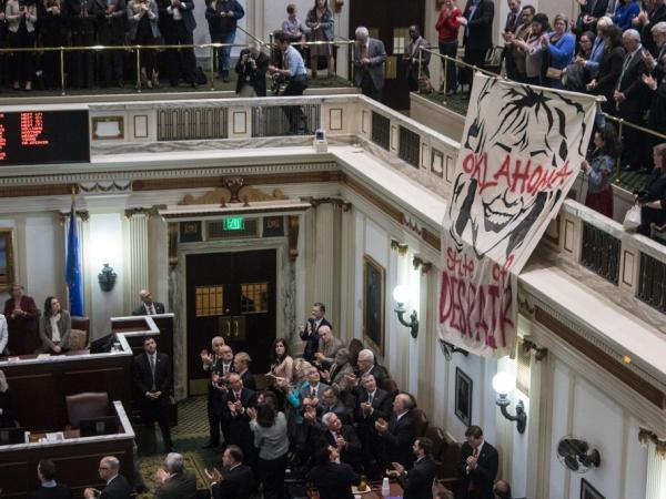 Protesters unfurl a caricature of Oklahoma Gov. Mary Fallin at the end of her State of the State address on Monday.