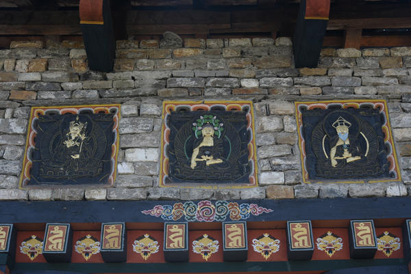 "A triptych depicts Lord Buddha (middle), Guru Rinpoche, known as the Second Buddha (left), and Zhabdrung Ngawang Namgyel (right), who unified Bhutan and whose title translates as ""at whose feet one submits."" The work is painted above the door of the National Memorial Stupa, a Tibetan-style temple in Bhutan's capital city Thimphu."