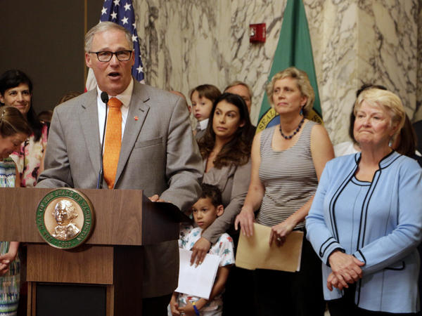 Washington Gov. Jay Inslee, surrounded by lawmakers and other supporters of paid family leave, speaks before signing a state law to guarantee such leave on July 5, 2017, in Olympia, Wash.