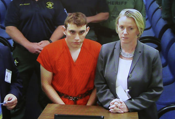 A video monitor shows school shooting suspect Nikolas Cruz, left, making an appearance before Judge Kim Theresa Mollica in Broward County Court Thursday in Fort Lauderdale.