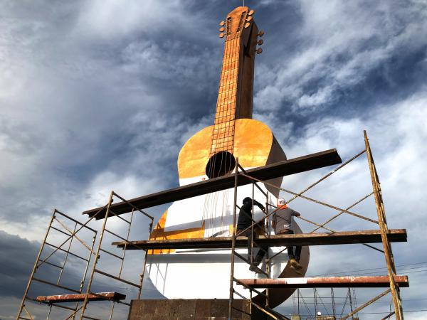 Workers cover a large bronze guitar statue in white. The statue sits at the entrance to the town of Paracho. This weekend, the town will pay tribute to German Vazquez, a former resident and master guitar maker from the town. Vazquez designed the white guitar featured in the movie <em>Coco</em>.