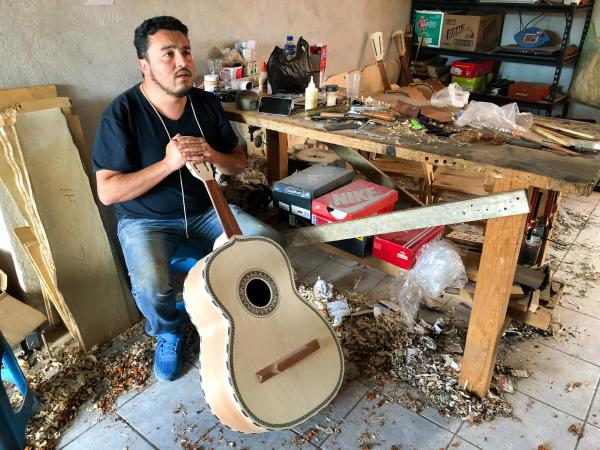 César Ivan Lemus, a third-generation Paracho artisan, shaves the neck of a <em>guitarrón</em> he's making. Lemus sells all types of instruments to mariachi schools and stores in the U.S. He says he's working as fast as he can to keep up with orders these days.