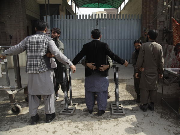 Loyalists of outlawed charities in Pakistan pat down worshipers before Friday prayers.