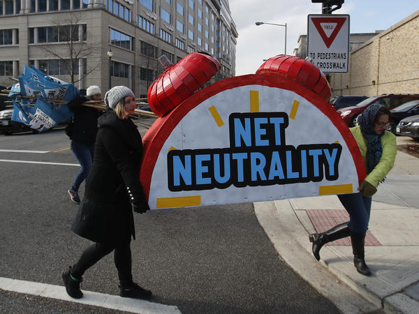 """Protesters Sammi LeMaster and Katherine Fuchs carry the top of an alarm clock display that reads """"Net Neutrality"""" after a demonstration at the Federal Communications Commission on Dec. 14, 2017."""