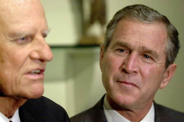 "George W. Bush, then as a Republican presidential candidate listens to the Rev. Billy Graham. Bush credits Graham with his ""born-again"" breakthrough."