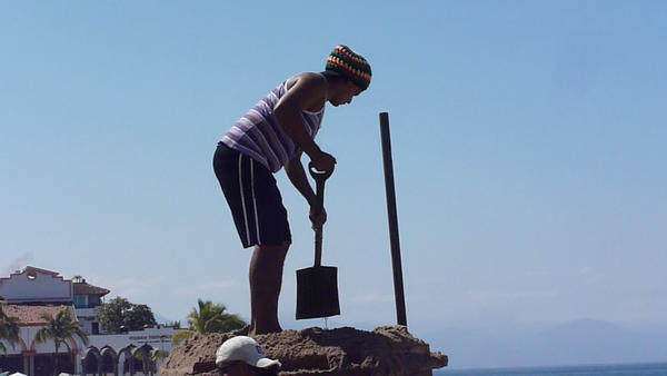 A man bends with a beautiful hip hinge in Puerta Vallarta, Mexico.