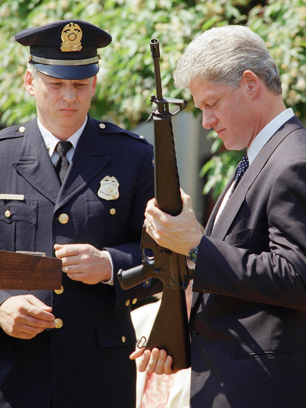 President Bill Clinton holds an AR-15 rifle during a White House ceremony in 1994 where he launched efforts to ban assault-style weapons. The ban was in place from 1994 to 2004. Dayton, Ohio Police Lt. Randy Bean, whose fellow officer was gunned down with an AR-15 in 1991, looks on.