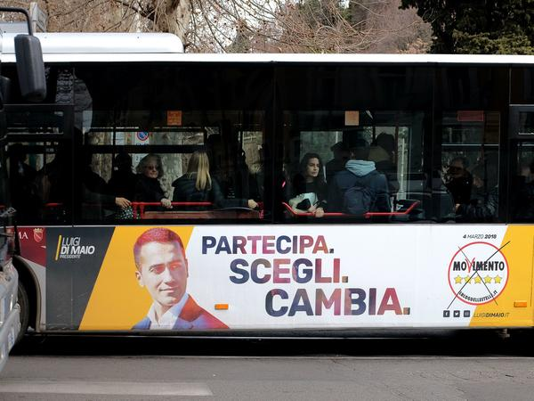 "An election poster for the 5-Star Movement showing leader Luigi di Maio and the motto ""Participate. Choose. Change"" is seen on the side of a bus in Rome ahead of the March 4 general elections."