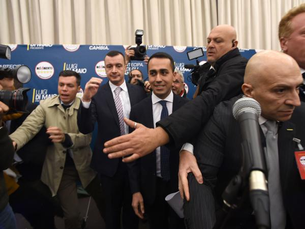 Italy's populist 5-Star Movement leader Luigi Di Maio (center) is surrounded by bodyguards as he arrives to give a press conference on Monday in Rome.