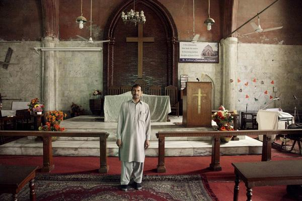 Salim Masih, the church caretaker, poses for a photo near the altar of the St. Andrew's United Presbyterian, built in 1860, during the British colonial period.
