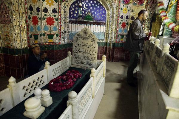 Men pray in the garlanded shrine of Mauj Darya.