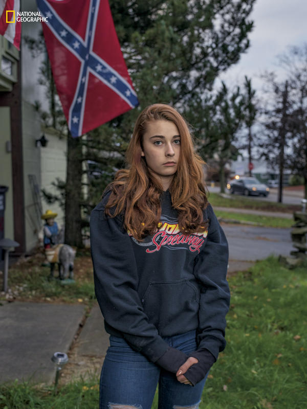 "Felyssa Ricco stands outside the house in Hazleton, Pa., where she lives with her mother and stepfather, Kelly and Jesse Portanova. In addition to flying Old Glory and other flags, such as ""Don't Tread on Me,"" the Portanovas sometimes fly the Confederate flag, saying it's a way of standing up to those who believe it shouldn't be displayed or who want to disregard America's history."