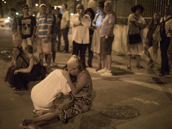 People cry on the sidewalk next to the scene where council member Marielle Franco and her driver were shot to death by two unidentified attackers in Rio de Janeiro on Thursday.