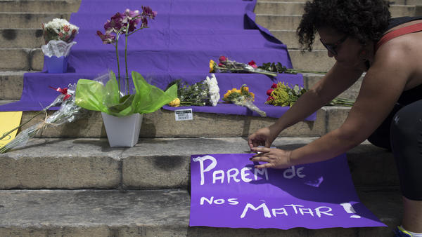"A woman positions a sign with a message that reads in Portuguese: ""Stop Killing Us!"" on the steps of City Hall where people gathered to pay their respects to slain council member Marielle Franco and her driver."