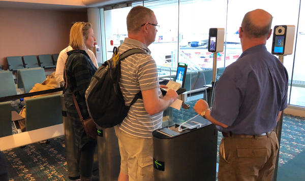 Passengers use facial recognition scanners before boarding a British Airways flight in Orlando, Fla.