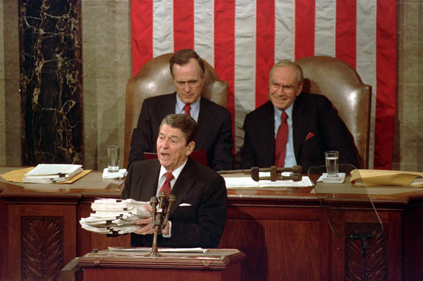 During his 1988 State of the Union address, President Ronald Reagan holds up a 14-pound continuing resolution for the budget, part of a total package weighing 42 pounds, which the president said was two months late from Congress. Vice President George H.W. Bush (left) and House Speaker James Wright of Texas listen behind him.