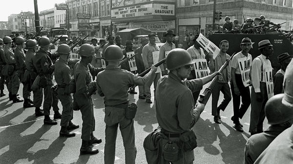 Striking sanitation workers and their supporters are flanked by bayonet-wielding National Guard troops and armored vehicles during a march on City Hall in Memphis, Tenn., on March 29, 1968, one day after a similar march erupted in violence, leaving one person dead and several injured.