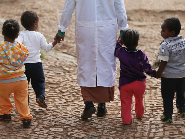 A woman walks with orphans at an Addis Ababa orphanage in 2013. The number of Ethiopian children adopted by Americans fell from 2,511 in 2010 to 133 in 2016, according to the State Department. Ethiopia's parliament banned all foreign adoption in January.