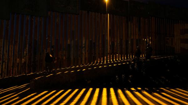 People walk near the fence of the Mexico-U.S. at Playas de Tijuana in northwestern Mexico.