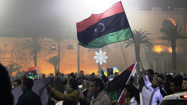 Demonstrators raise Libyan flags at a national unity demonstration in Tripoli's Martyrs' Square in 2012.