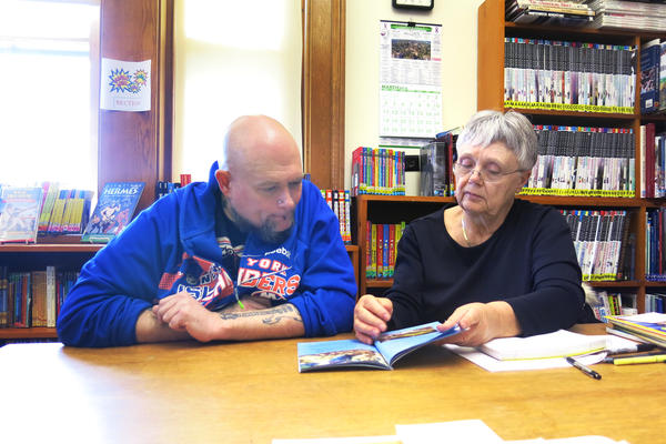 Robert Hartmann meets with his tutor, Sandy DeLuck, at the public library in Winterport, Maine. Hartmann reads at about a first-grade level.