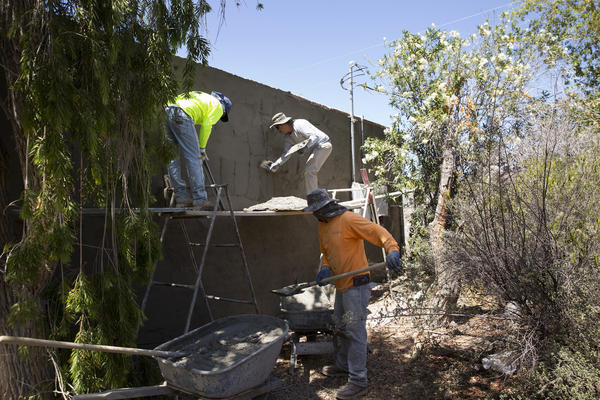 Contractors apply stucco to the exterior of a home being renovated by Rosin and Pickett. Ten years into her career flipping houses, Rosin's operation is much more streamlined and professional. Still, it's harder to make money.