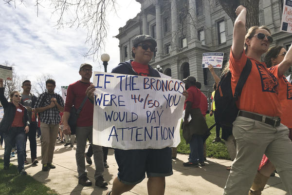 Colorado teachers rally on April 16 outside the state Capitol to demand more funding for schools and oppose changes to the state's pension system.
